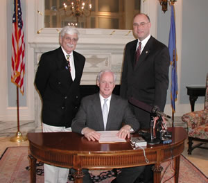 Gov. Frank Keating, with Sen. Ben Robinson (left) and Rep. Ray Vaughn (right) watching, signs SB 1553