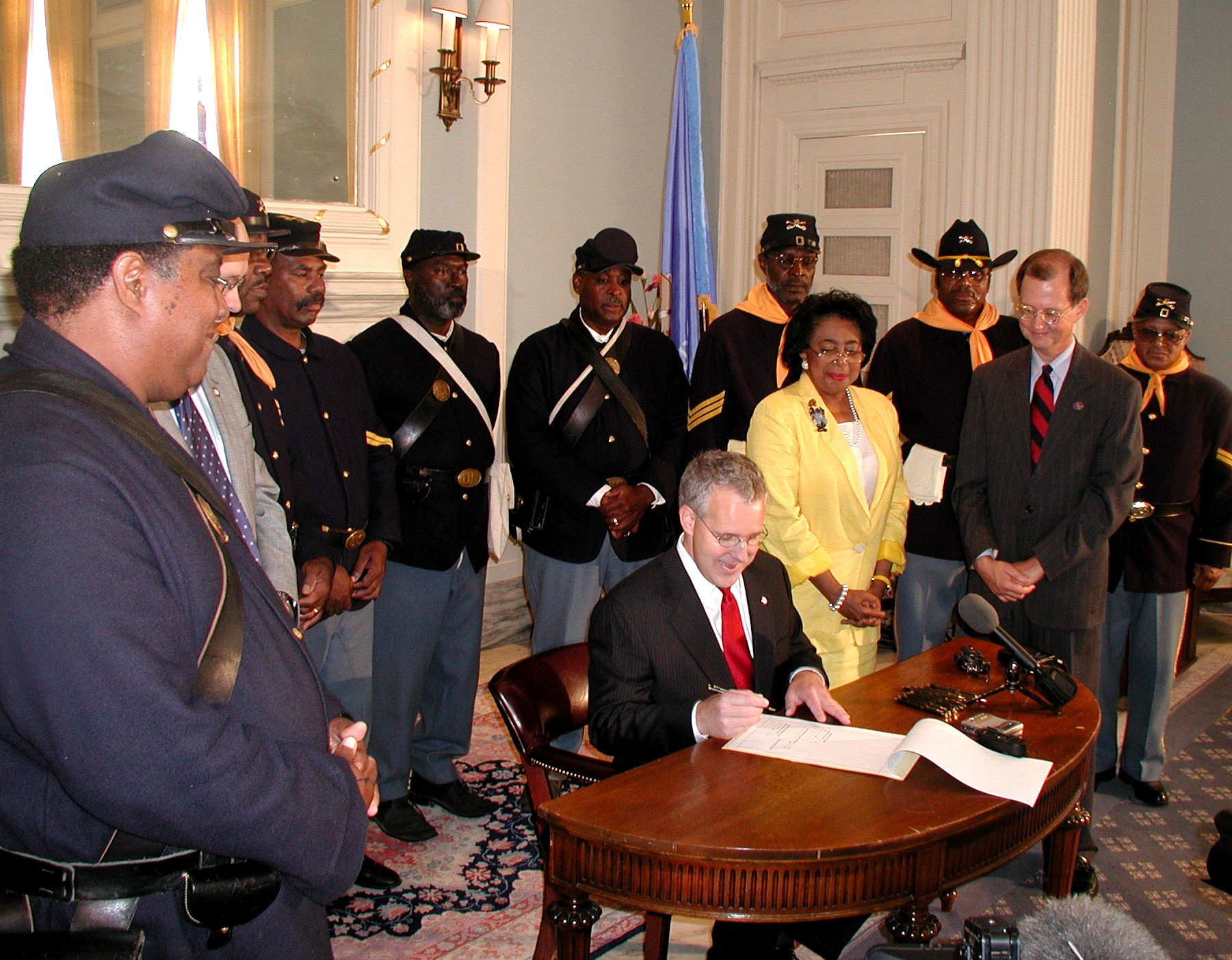 Sen. Eason McIntyre and the Buffalo Soldiers watch Gov. Henry sign the bill.